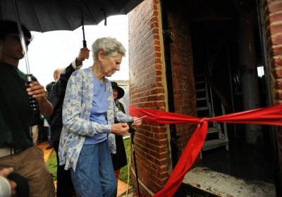 Amalie Cass, a summer resident of Aquinnah, cuts the ribbon at the door to Gay Head Light before it was re-lit. Cass was the lead donor to the project to relocate the 400-ton lighthouse some 135 feet from the edge of the Gay Head Cliffs earlier this year. Merrily Cassidy/Cape Cod Times